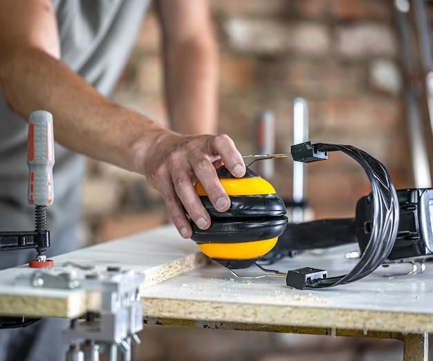 Trabalho de carpinteiro profissional com fones de ouvido protetores, proteção pessoal para trabalho em oficina de produção de madeira.
