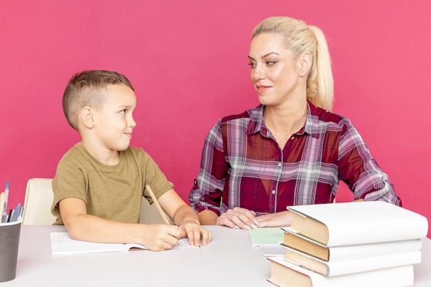 Trabalho de casa à distância com a mãe em casa na hora da quarentena. menino com a mãe sentada na mesa e estudando.