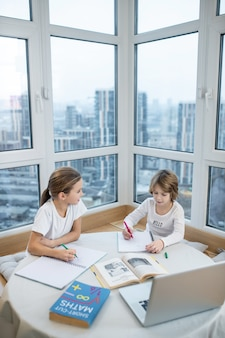 Trabalho de casa. menina bonitinha e menino em idade escolar em roupas leves, sentado à mesa com livros e laptop escrevendo, estudando em casa