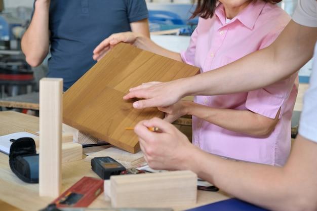 Trabalho de close-up em oficina de móveis de carpintaria, mãos de trabalhadores com amostras de madeira