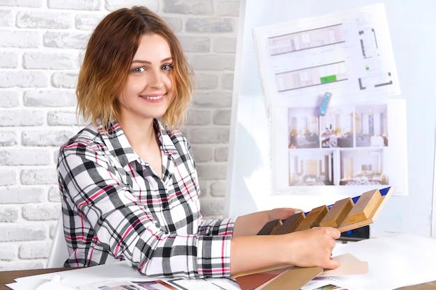 Trabalho de designer de interiores jovem freelancer desenvolver novo projeto de apartamento no estúdio de design. reunião feminina de mulheres menina com mesa de reunião com desenhos de desenhos e rascunhos de novo projeto