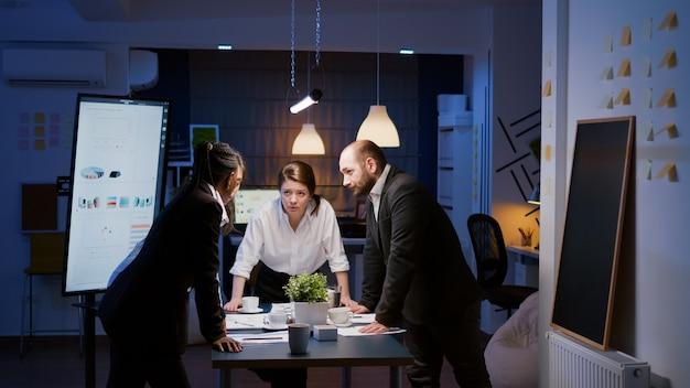 Trabalho de equipe multiétnico diversificado em pé ao redor da mesa, debatendo ideias de empresas, verificando a papelada de estatísticas de gerenciamento. colegas de trabalho concentrados planejando apresentação de negócios em horas extras na sala de reuniões