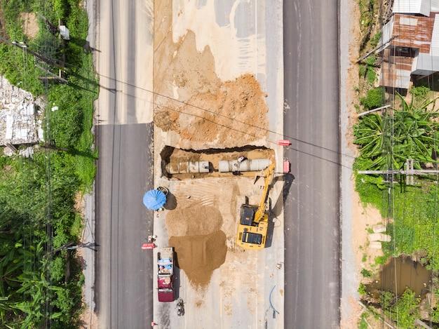 Trabalho de escavadeira de tubulação de água por retroescavadeira e trabalhadores