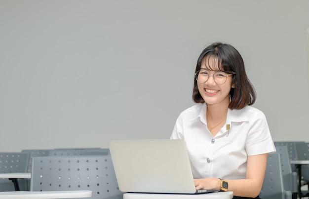 Trabalho de estudante bonito com laptop em sala de aula