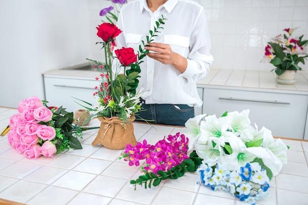 Trabalho de florista jovem, organizando a flor artificial diy, o artesanato e o conceito feito à mão.