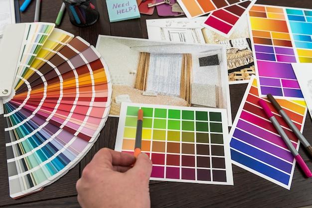 Trabalho de homem com paleta de cores e esboço de apartamento de casa para casa de design criativo. plano de renovação do arquiteto
