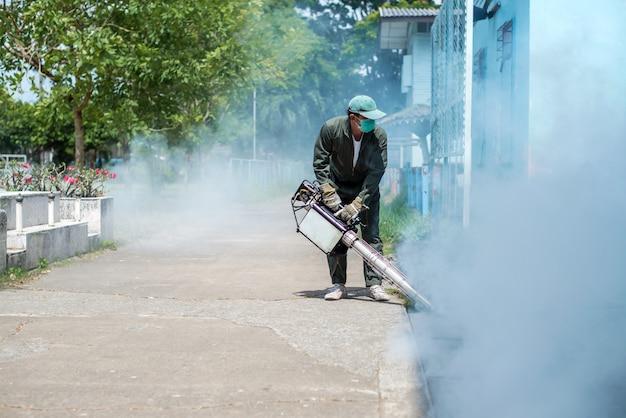 Trabalho de homem nebulizando para eliminar o mosquito para prevenir a disseminação da dengue e do vírus zika