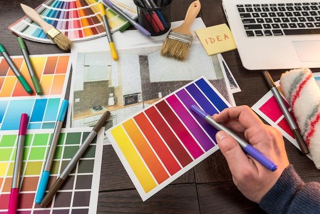 Trabalho de mão masculino com classificador de cores para casa de design. esboço do apartamento na mesa do escritório