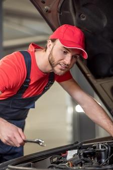 Trabalho de mecânico de automóveis. jovem barbudo com uma chave inglesa olhando com interesse para o capô aberto de um carro em uma oficina mecânica