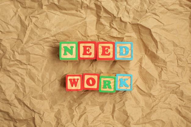 Trabalho de necessidade feito de letras de madeira na parede de papel reciclado marrom amassado.