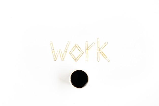 Trabalho de palavras feito de clipes dourados e café em uma composição minimalista plana