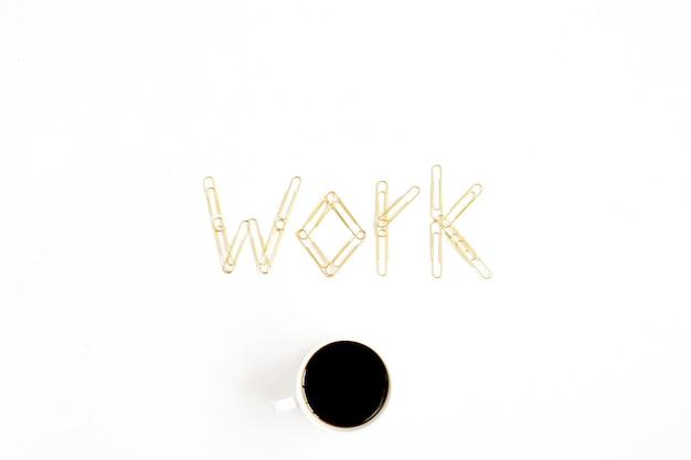 Trabalho de palavras feito de clipes dourados e caneca de café
