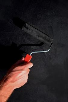 Trabalho de pintura com um rolo de pincel em preto