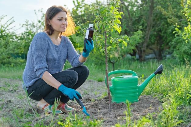 Trabalho de primavera no jardim, garrafa de fertilizante químico, fungicida na mão