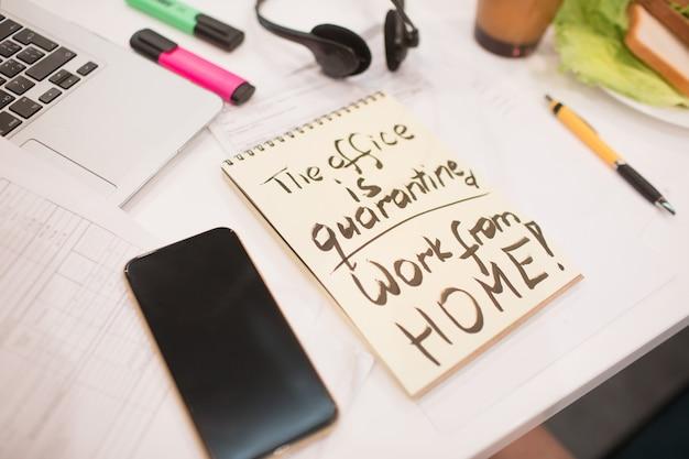 Trabalho de quarentena de escritório de inscrição em casa em papel amarelo em um notebook