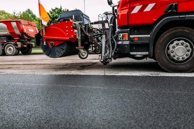 Trabalho de reparação de estradas. espanador ao reparar a estrada. máquina de limpeza de ruas.
