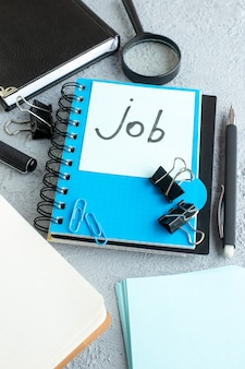 Trabalho de vista frontal escrito nota com bloco de notas e caneta sobre fundo claro