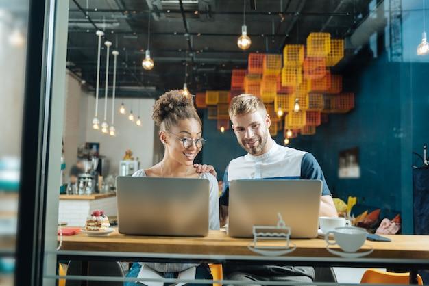 Trabalho distante. dois freelancers bonitos e sorridentes fazendo seu trabalho distante enquanto estão sentados em uma padaria