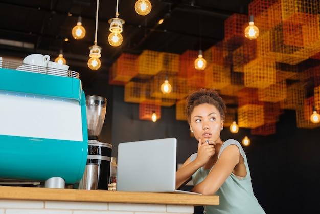 Trabalho distante. mulher de cabelos escuros e cacheados se sentindo pensativa enquanto faz um trabalho distante, sentada no refeitório