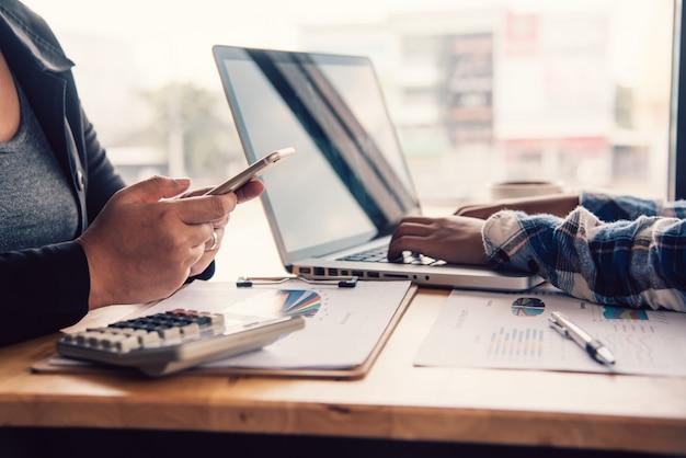 Trabalho do empresário de equipe. trabalhando com laptop e documento para financeiro no escritório de espaço aberto. relatório da reunião em andamento