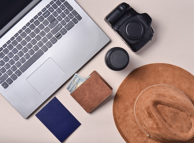 Trabalho do fotojornalista. laptop, carteira, passaporte, chapéu, câmera, lente. conceito de viagens, vista superior, plana leigos