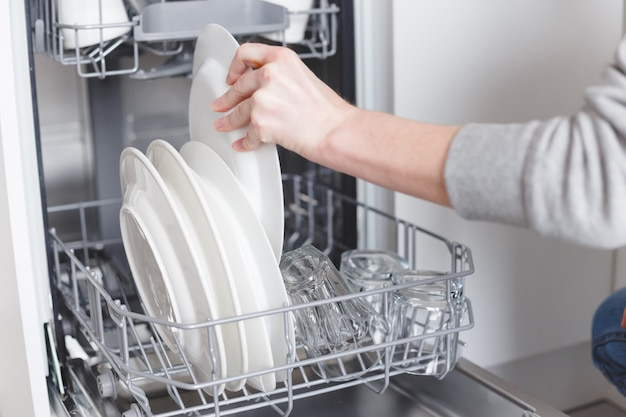Trabalho doméstico: jovem mulher colocando pratos na máquina de lavar louça