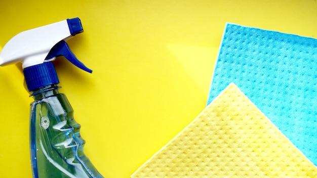 Trabalho doméstico, tarefas domésticas e conceito doméstico - pano de limpeza, spray de detergente em fundo amarelo