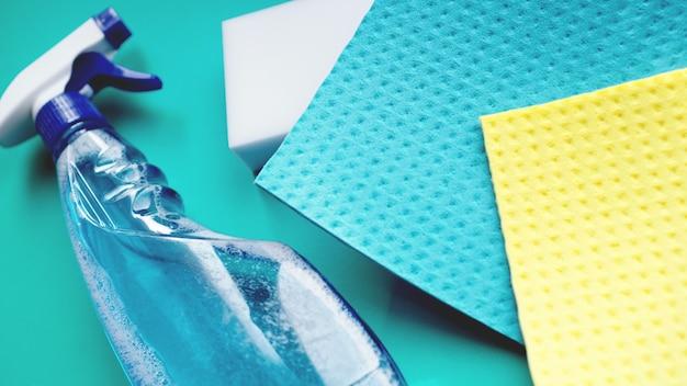 Trabalho doméstico, tarefas domésticas e conceito doméstico - pano de limpeza, spray de detergente no fundo azul