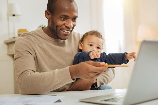 Trabalho e babá. belo alerta barbudo homem afro-americano sorrindo e trabalhando no laptop enquanto uma criança está sentada em seu colo