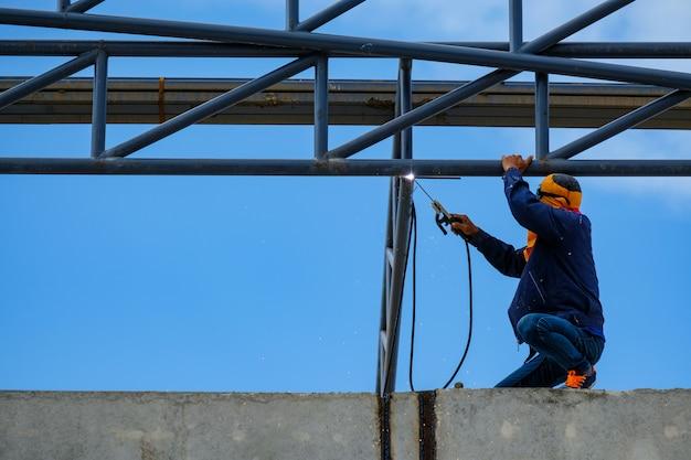 Trabalho em altura, estrutura de soldagem homem de telhado de fábrica no canteiro de obras