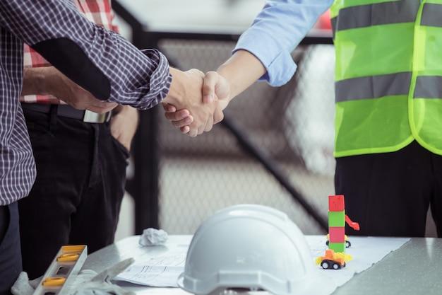 Trabalho em equipe, apertando as mãos no canteiro de obras