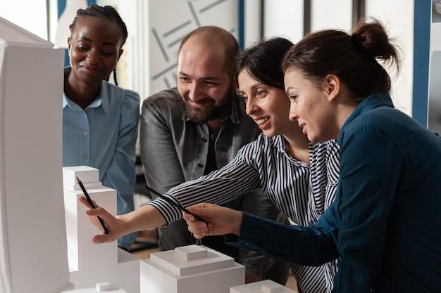 Trabalho em equipe arquitetônica multiétnica analisando maquete