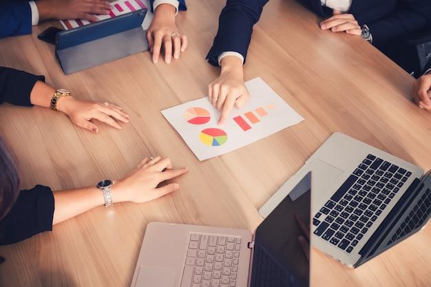 Trabalho em equipe com gráfico de custo de análise de pessoas de negócios na sala de reunião