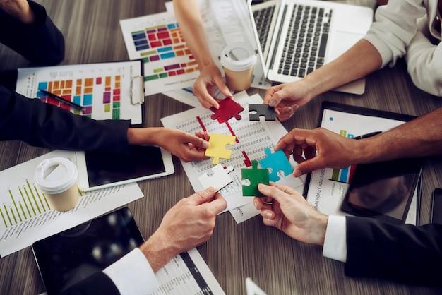 Trabalho em equipe com muitas mãos que combinam as peças de um quebra-cabeça