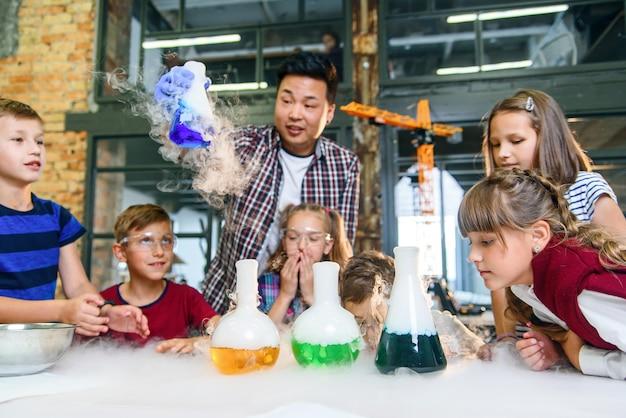 Trabalho em equipe de crianças em idade escolar e seu professor com experimento químico no moderno laboratório bem equipado.
