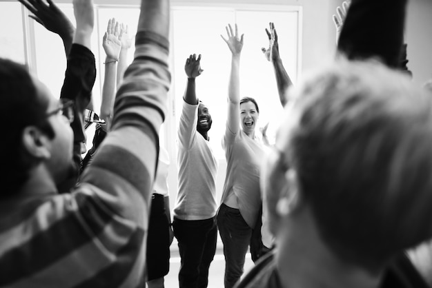 Trabalho em equipe de diversidade com as mãos levantadas