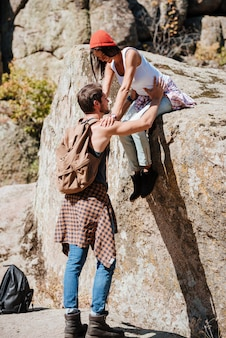 Trabalho em equipe de homem e mulher escalando ou caminhando no verão