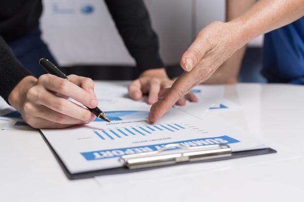 Trabalho em equipe de mulheres de negócios estão ajudando a analisar relatórios de negócios