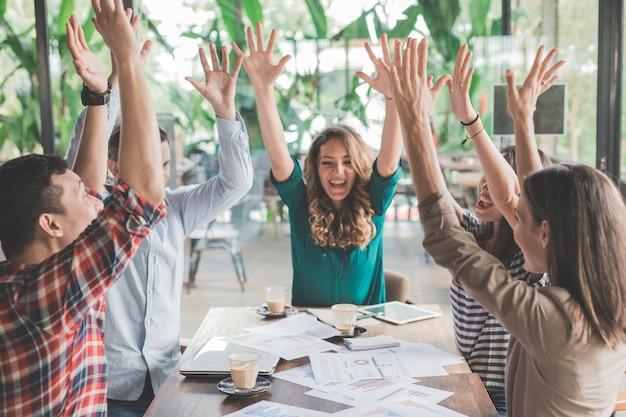 Trabalho em equipe de negócios de plano criativo é bem-sucedido e levanta as mãos