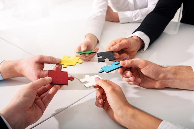 Trabalho em equipe de parceiros. conceito de integração e inicialização com peças de quebra-cabeça