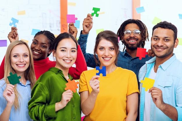 Trabalho em equipe de parceiros que trabalham juntos. conceito de integração e inicialização com peças de quebra-cabeça coloridas