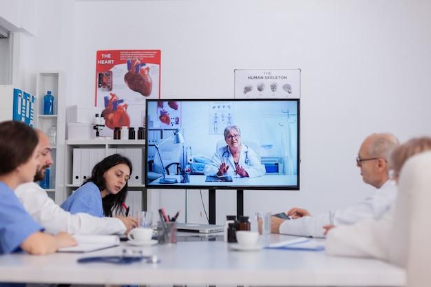 Trabalho em equipe discutindo tratamento de doenças durante teleconferência de videochamada online e telemedicina trabalhando em sala de reunião