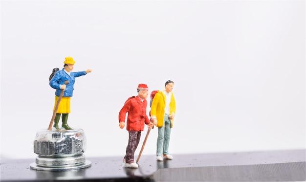Trabalho em equipe do viajante em miniatura e mochileiro isolado no fundo branco, sucesso do trabalho em equipe de liderança nos negócios