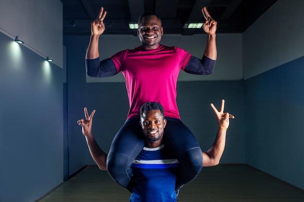 Trabalho em equipe dois bonito desportista afro-americano no boxe em um fundo preto no ginásio, treinador e ala praticando boxe