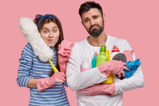 Trabalho em equipe e conceito de limpeza. uma jovem e um homem descontentes veem um quarto sujo com desprazer, usam material de limpeza