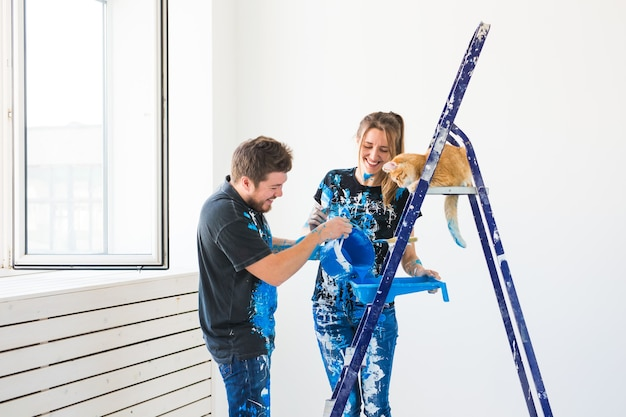 Trabalho em equipe e conceito de reparo jovem casal com gato fazendo uma reforma em um apartamento novo