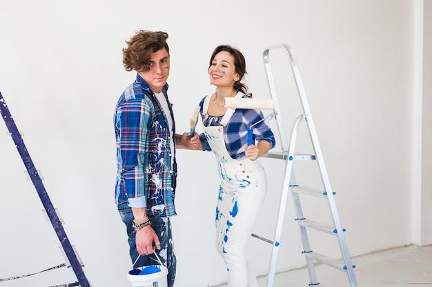 Trabalho em equipe e conceito de reparo jovem casal fazendo uma reforma em um apartamento novo