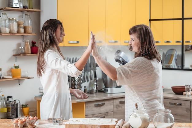 Trabalho em equipe em família, mãe e filha cozinhando juntas