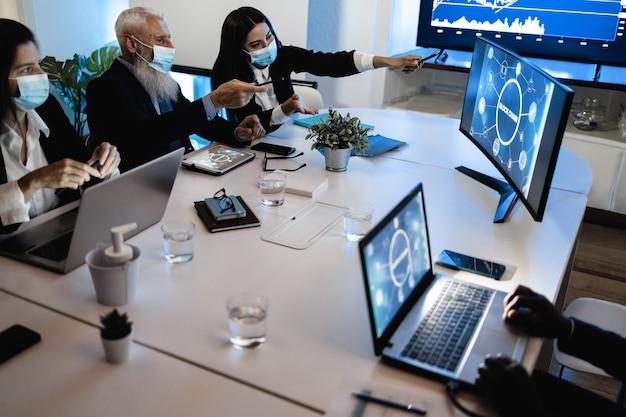 Trabalho em equipe fazendo reunião dentro do escritório da empresa fintech usando máscara de segurança durante surto de coronavírus - foco principal na mão direita da mulher