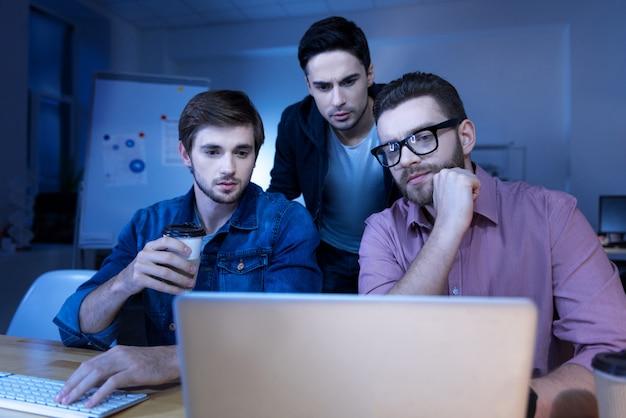 Trabalho em equipe. homem bonito e inteligente pensativo olhando para a tela do laptop e pensando em seu projeto enquanto trabalham juntos